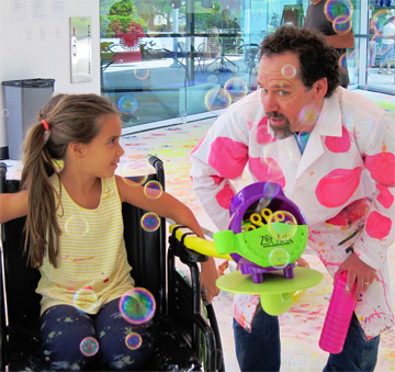 Photo taken by Irene Sperber.<br/>  Dwayne Szot demonstrating his bubble chair machine at All Kids <br/>Included Family Fun Day.