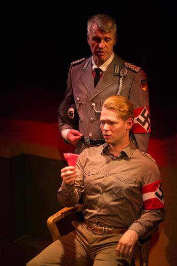 Herr Zeller (Michael Kehr, standing), shows tough love toward Rolfe Gruber (Jordan Armstrong) in