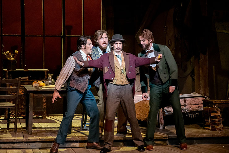 The supporting bohemians are bass Simon Dyer as the philosopher Colline and baritone Benjamin Dickerson as the feisty top-hatted musician Schaunard, shown with Treveor Schenemann as Marcello and Alesandro Scotto di Luzio as Rodolfo. Photographer: Chris Kakol